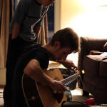 Ben re-stringing Taylor's guitar while Caleb looks on.