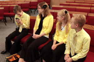 """Sam pretending to be cool and engrossed on a """"phone"""" – the others are unimpressed."""